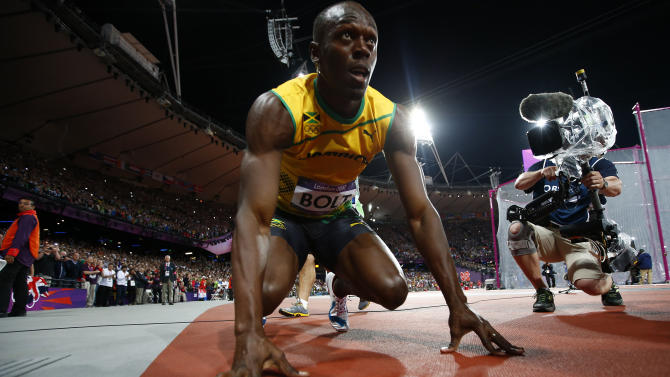 Jamaica's Usain Bolt crouches on track after winning  men's 100m final at London 2012 Olympic Games