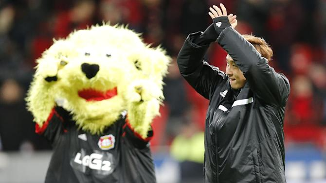 Leverkusen's Son Heung-min of South Korea celebrates with the team mascot after winning the German first division Bundesliga soccer match between Bayer Leverkusen and Hamburg SV in Leverkusen, Germany, Saturday, Nov. 9, 2013