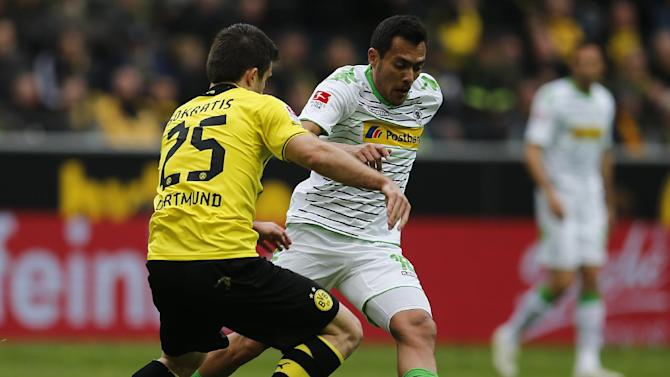 Dortmund's Sokratis of Greece, left, and Moenchengladbach's Raffael of Brazil challenge for the ball during the German first division Bundesliga soccer match between BvB Borussia Dortmund and VfL Borussia Moenchengladbach in Dortmund, Germany, Saturday, March 15, 2014