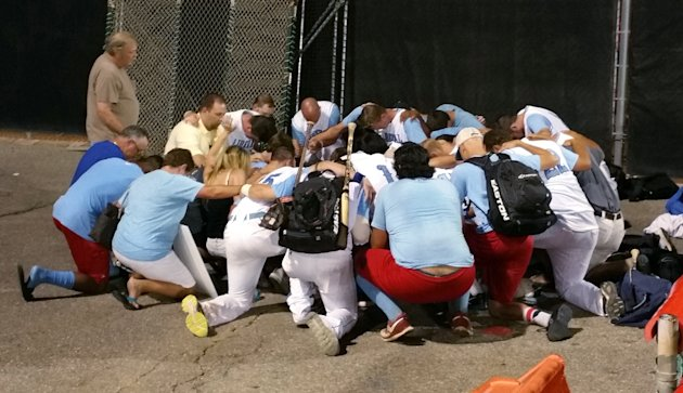 In this Aug. 2, 2015 photo, Liberal Bee-Jays teammates and staff gather after their game Sunday to remember Kaiser Carlile, their 9-year-old bat boy who died during a National Baseball Congress World Series baseball game in Wichita, Kan. The boy was hit in the head by a follow-through swing near the on-deck circle on Saturday. A league spokesman says Kaiser was wearing a helmet, which is mandatory. (Taylor Eldridge/The Wichita Eagle via AP) LOCAL TV OUT; MAGS OUT; LOCAL RADIO OUT; LOCAL INTERNET OUT