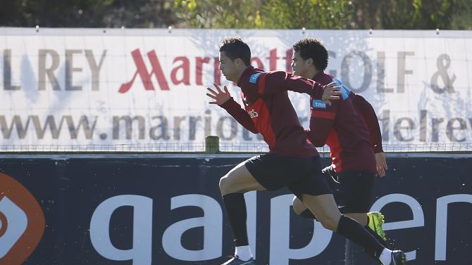 Portugal's Cristiano Ronaldo runs beside his teammate Pepe during a training session in Obidos