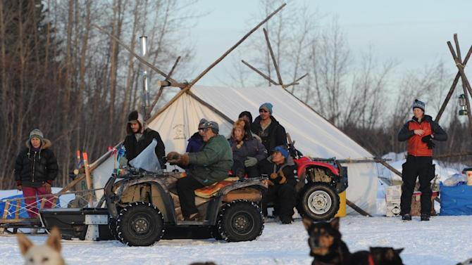 People from the Athabaskan village of Nikolai, Alaska, take a look at the Iditarod sled dog teams parked on the banks of the Kuskokwim River on Tuesday, March 5, 2013. (AP Photo/Bill Roth, Anchorage Daily News)