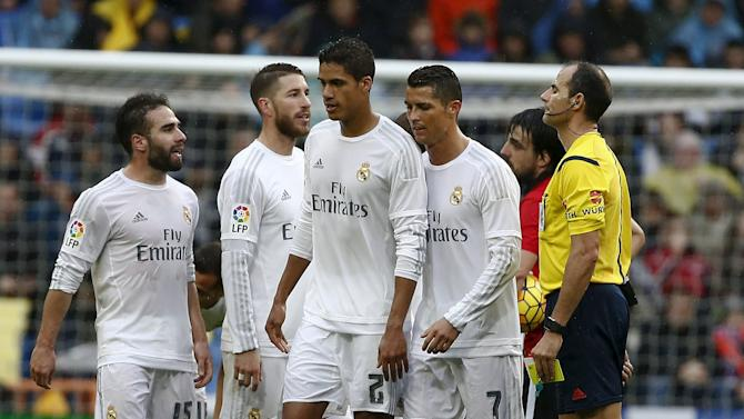 Real Madrid's Raphael Varane leaves the field next to teammate Cristiano Ronaldo after receiving two yellow cards