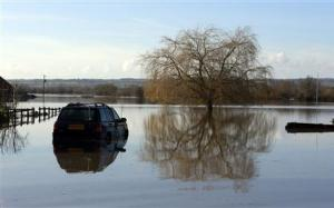 A semi submerged car is seen in urban landscape taken in the flooded Somerset village of Moorland