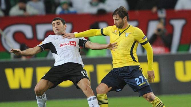 Legia Warszawa's Vladimer Dvalishvili, left, and Lazio's Lorik Cana challenge for the ball during their Europa League Group J soccer match between Legia Warszawa and Lazio Rome,  in Warsaw, Poland, Thursday, Nov. 28, 2013