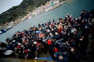 People gather near the commemorative board in the port of the Italian island of Giglio on January 13, 2013. Survivors, grieving relatives and locals on the island of Giglio gathered Sunday to mark the first anniversary of the Costa Concordia cruise ship disaster, which claimed 32 victims