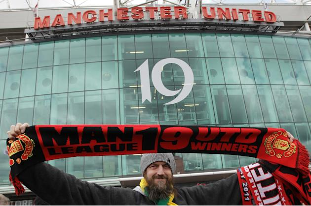 FILE - In this May 22, 2011 file photo, a Manchester United fan holds up a scarf displaying Manchester United's 19 league titles ahead of the English Premier League soccer match between Manchester Uni