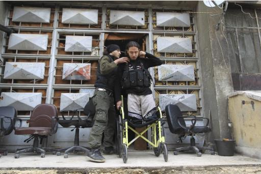Abu Nejme, a 21-year-old Free Syrian Army fighter, stands in his wheelchair in Aleppo