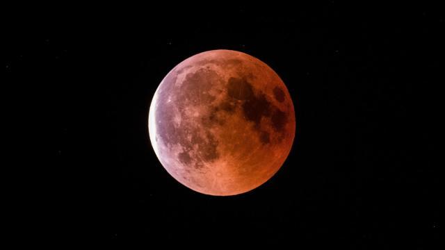 Der teilweise vom Erdschatten verdunkelte Vollmond leuchtet während einer Mondfinsternis rot bis orange. Foto: Silas Stein/Archiv