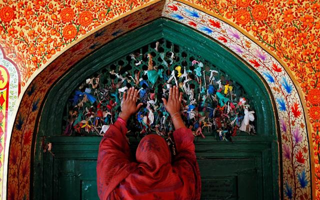 A woman prays at the shrine of Sufi Saint Khawaja Naqshband during the holy fasting month of Ramadan in Srinagar last year - REUTERS