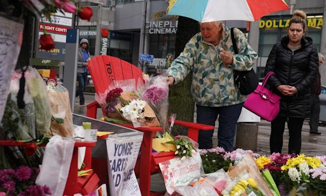 A woman pays her respects at a makeshift memorial following the Toronto attack.