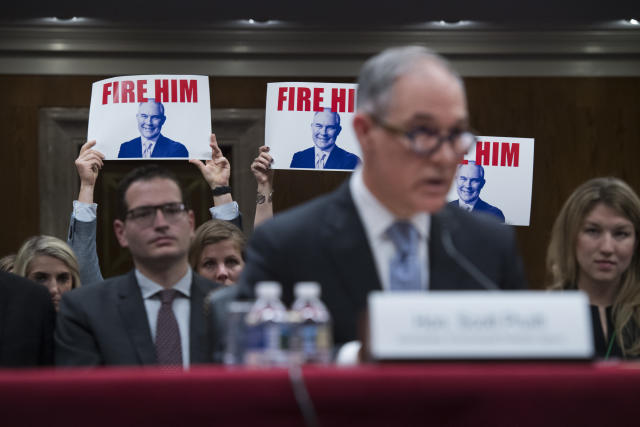 Protesters hold signs as Pruitt testifies during a Senate hearing on the proposed fiscal year 2019 budget for the EPAin May 2018. (Tom Williams/CQ Roll Call via Getty Images)