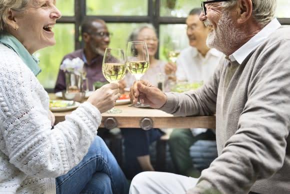 Senior couple toasting with glasses of white wine