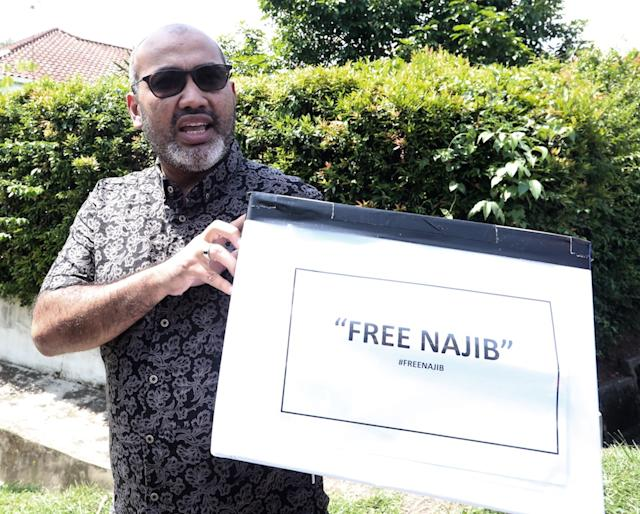Ghulam Muzaffar Gulam Mustakim holds up a box with the words 'Free Najib' for the launch of a donation drive for the embattled former prime minister. — Picture from China Press