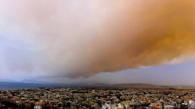 Eine Rauchwolke färbt Teile des Himmels über Athen orange. Bei extremer Trockenheit und starken Winden ist ein Waldbrand nahe der griechischen Ferienortschaft Kineta außer Kontrolle geraten. Foto: Aristidis Vafeiadakis/ZUMA Wire