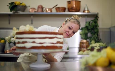 Claire Ptak puts the finishing touches to Prince Harry and Meghan Markle's cake - Credit: Hannah McKay