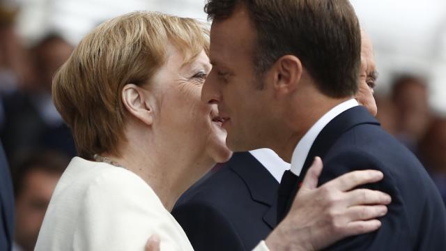Frankreichs Präsident Emmanuel Macron begrüßt Angela Merkel während der großen Militärparade auf der Prachtstraße Champs-Élysées. Foto:Kamil Zihnioglu/AP