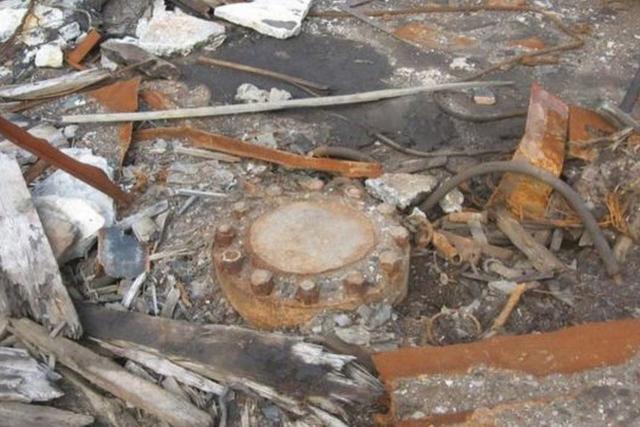 En mitad del edificio desmoronado hay una tapa metálica pesada y oxidada incrustada en el piso de hormigón
