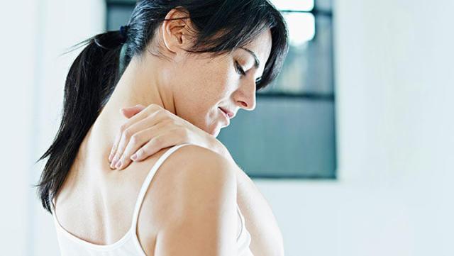 Person rubbing their shoulder