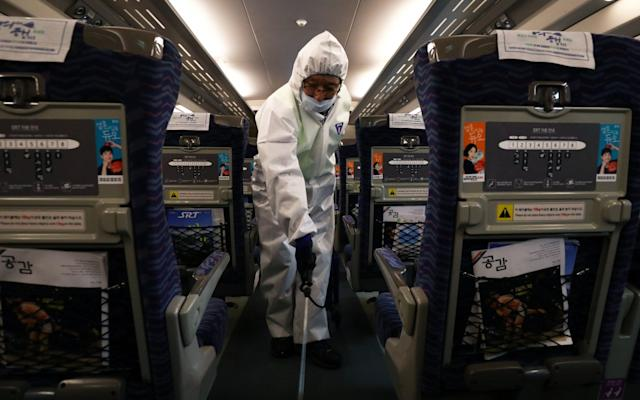 A disinfection worker sprays down a train in Seoul. The virus has spread across southeast Asia - Getty Images AsiaPac