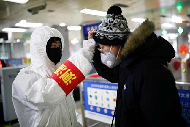 A staff member checks the temperature of a passenger entering a subway station, as the country is hit by an outbreak of the new coronavirus, in Beijing, China January 28, 2020. REUTERS/Carlos Garcia Rawlins