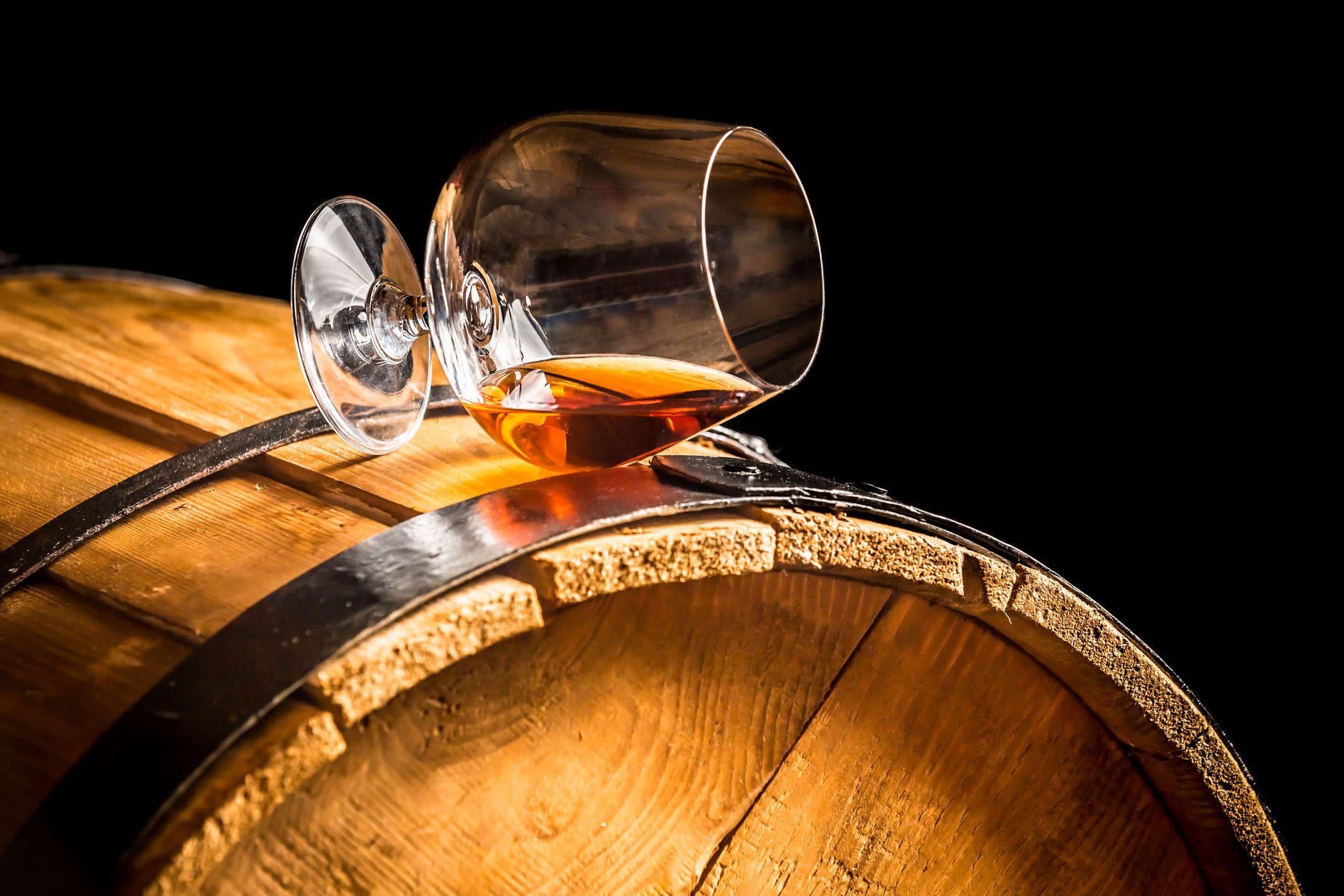 Glass of cognac on the vintage barrel
