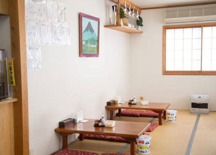 乾淨明亮的店內環境。桌上備有菜單、醬油、七味粉、炸麵球以及「すりだね」。