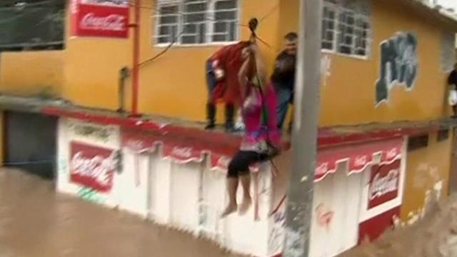 Locals use ziplines to cross Mexico's flooded roads