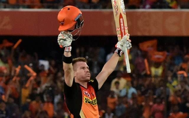 Warner raises his bat to celebrate a century as his fans throng in the background
