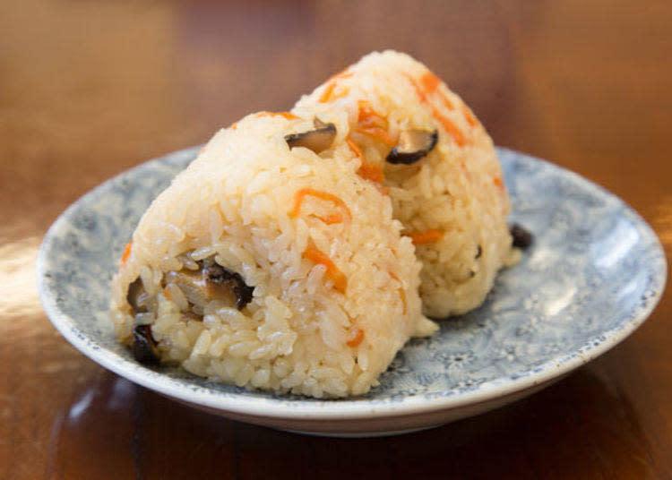 炊飯飯糰(180日圓・含稅)。香菇及紅蘿蔔混入飯內一起炊煮,吃得到食物本身的甘甜。很多人除了烏龍麵之外也會點這道喲。