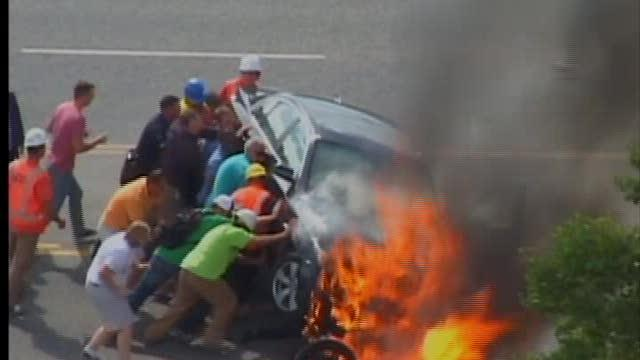 Bystanders pull man from burning car