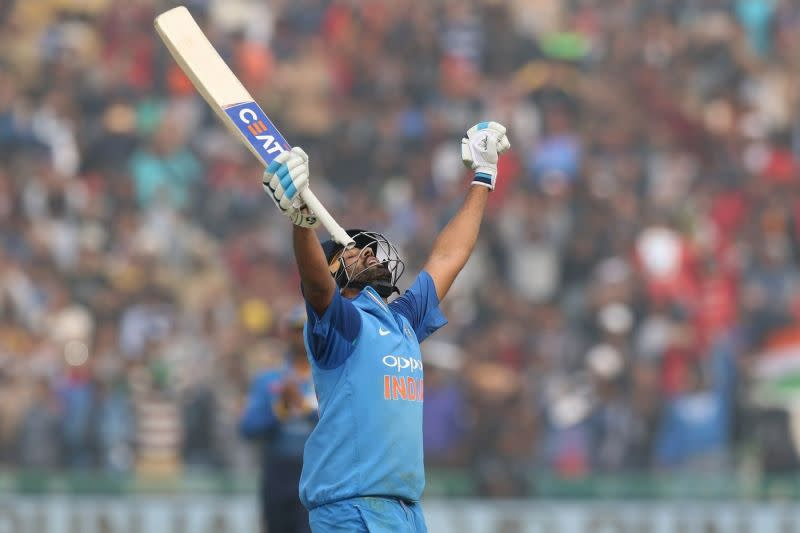 Rohit Sharma raises his bat after scoring his third double hundred