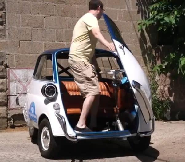 一名男子用開冰箱門的方式上車,接著直接將一部超可愛小車開走,這部車叫做BMW Isetta 。(圖片來源:https://www.facebook.com/BusinessInsider.Cars/videos/483269878751987/)