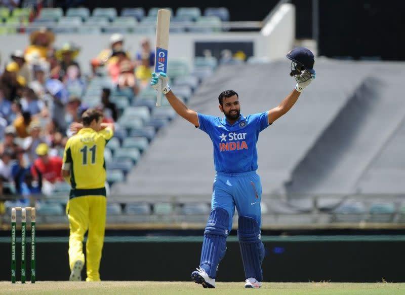 Rohit Sharma raises his bat after scoring a century