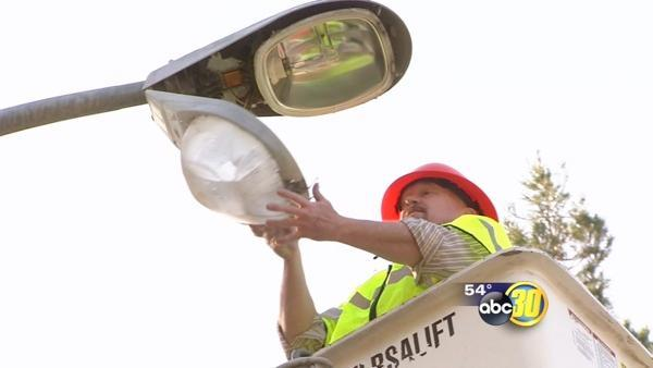 A city official replaces burned out street lights