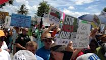 Protesters greet Gov. Rick Scott upon his arrival in St. Lucie County on Tuesday