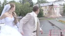 Building Collapses Behind Wedding Couple