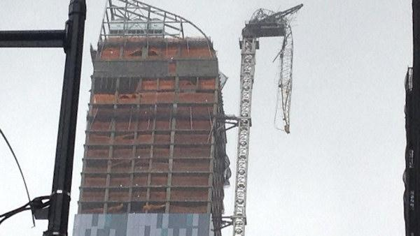 Crane dangling from a high rise apartment complex under construction