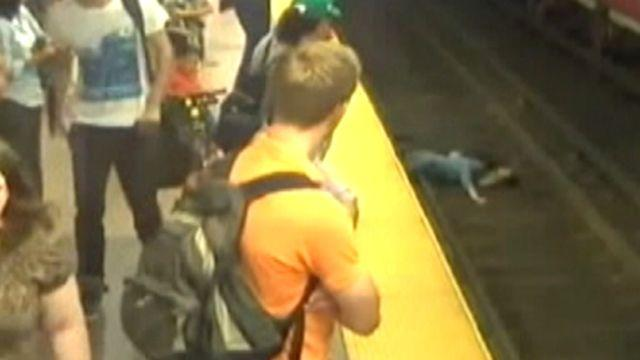Watch your step! Mom carrying son falls onto train tracks