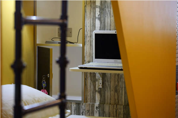 床頭貼心的提供行李箱櫃以及摺疊桌。(圖片來源/蜂巢膠囊旅店)