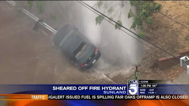 Sheared Hydrant Spews Water Onto Car