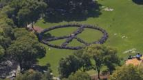 Thousands gather for human peace sign world record attempt