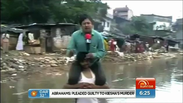 Journalist reports on top of flood survivor's shoulder