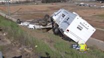 Truck with trailer rolls down freeway embankment in Fresno
