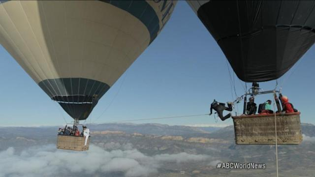 Daredevils Walk Tightrope Between Two Hot Air Balloons