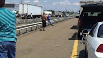 People Play Football on New Jersey Turnpike During Traffic Jam