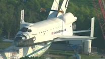 Space shuttle replica hoisted for landmark exhibit