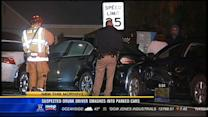 Suspected drunk driver smashes into parked cars