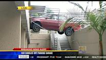 Car dangles off parking garage