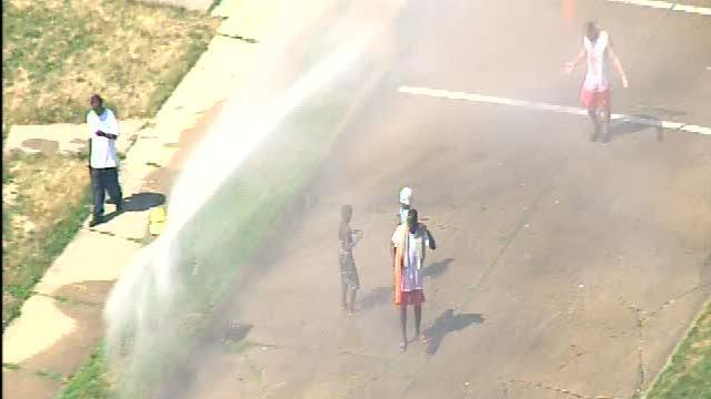 Residents in Detroit cool off under hydrant